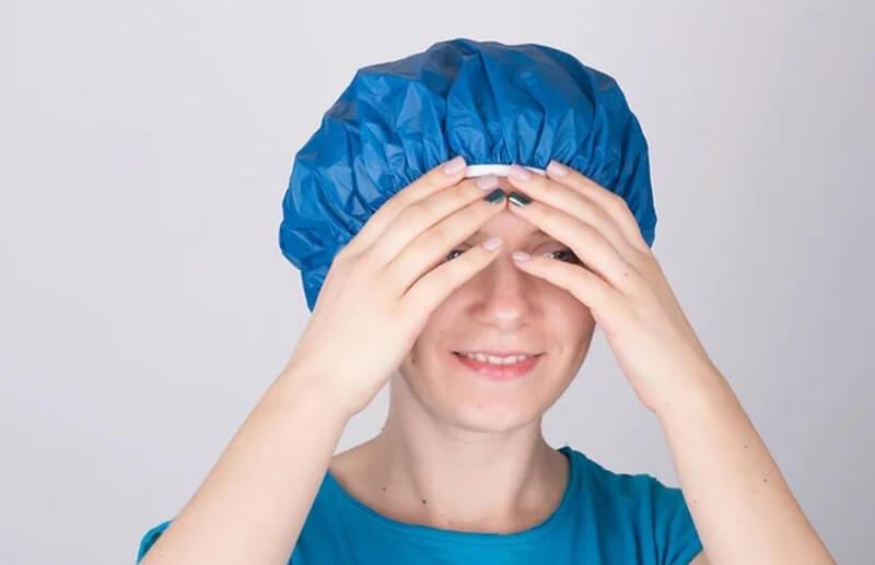 Trùm mũ tắm lên tóc và chờ mặt nạ thấm.