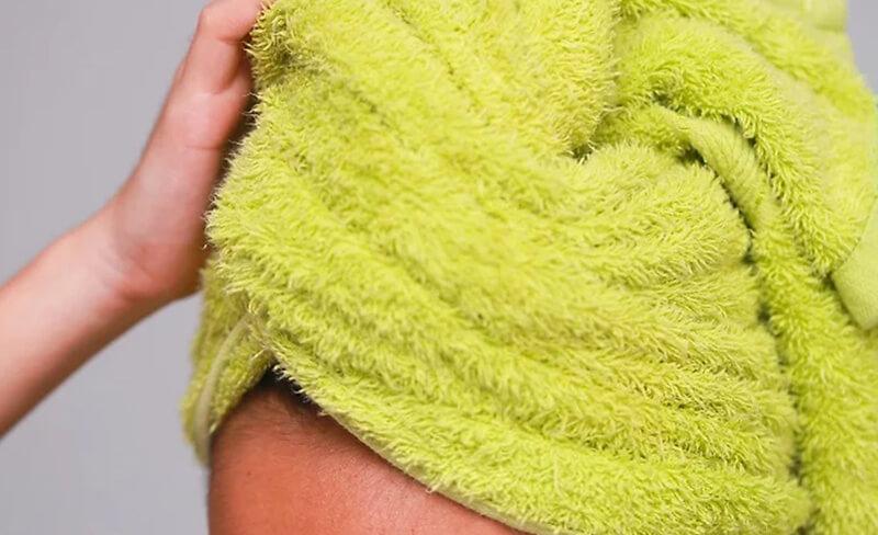 Lau khô tóc bằng khăn mềm.